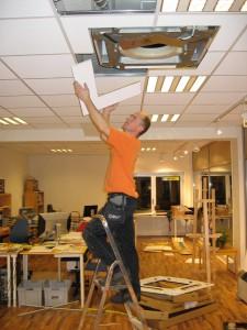 Mann på stige for å installere luft til lufte-anlegg