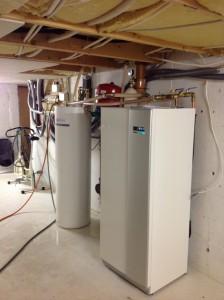 En akkumulatortank og en varmepumpe ved siden av hverandre i en kjeller